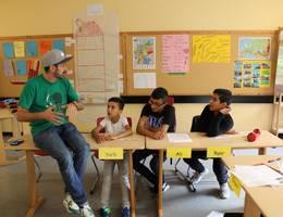 Die Schülerinnen und Schüler der Sprachlernklasse erarbeiten in der Albert-Einstein-Schule mit dem Rapper Spax den Songtext.