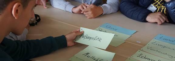 Teilnehmer des Projektes schauen sich Präsentationskarten an