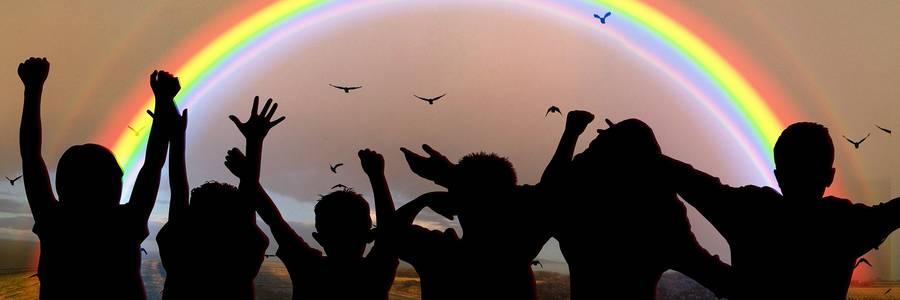 Kinder recken ihre Arme vor einem Regenbogen in die Höhe
