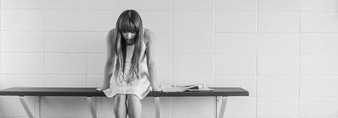 Ein deprimiertes Mädchen sitzt auf einer Bank