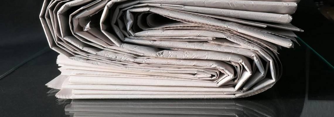 Ein Zeitungsstapel symbolisiert die Presse- und Öffentlichkeitsarbeit