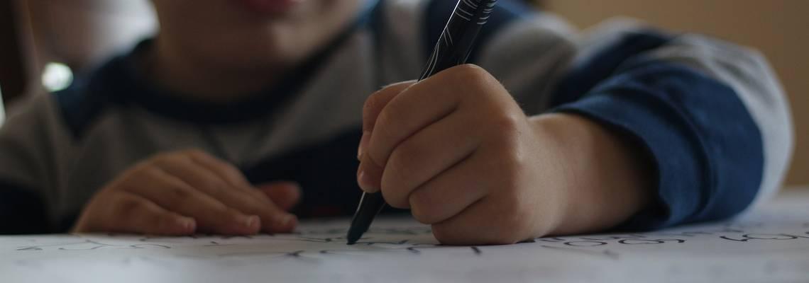 Ein Kind schreibt etwas auf ein Blatt Papier