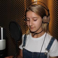 Eine Schülerin der Sprachlernklasse der Albert-Einstein-Schule singt im Tonstudio den Text für den Song ein.