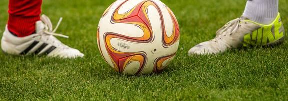 Zwei Fußballspieler stehen sich an einem Ball gegenüber