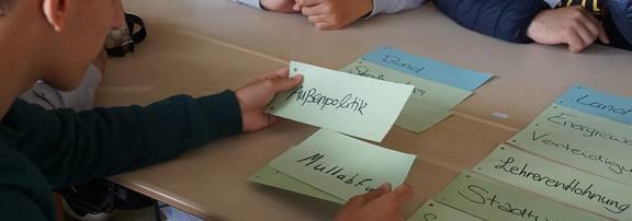 Schüler sitzen an einem Tisch und schauen sich Unterlagen an