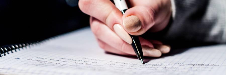 Eine Frau schreibt in ein Notizheft [(c): Daniel Junker]